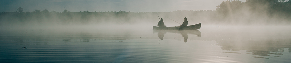 Two fisherman in a canoe on a misty lake at dawn