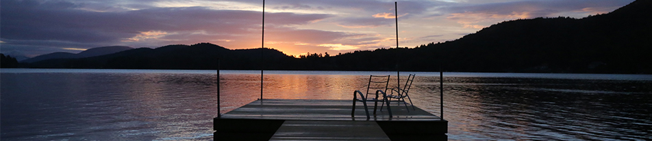 Two chairs sit on a floating dock in a serene lake at sunset